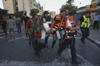 Israeli security forces and paramedics carry a wounded Jewish man after he was shot during violent unrest in Lod, Israel, Thursday, May 13, 2021. The man was shot, allegedly by an Arab man, during violent clashes between Jews and Arabs in the central city of Lod, Israeli media reported. (AP Photo/Ofer Vaknin)