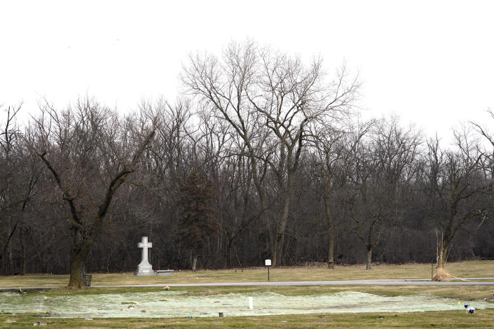 A lone cross monument rises above other horizontal graves markers Wednesday, March 17, 2021, on the northern edge of the historic Mount Glenwood cemetery in Glenwood, Ill. The cemetery was formed in 1908 by a group of Black businessmen with an explicit nondiscrimination clause in its charter. (AP Photo/Charles Rex Arbogast)