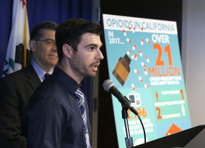 Jordon Basileu, right, flanked by California Attorney General Xavier Becerra, left, discusses how he became addicted to opioid painkillers, during a news conference, Monday, June 3, 2019, in Sacramento, Calif. Becerra announced, Monday that his office has filed a lawsuit against the maker of Oxycontin, Purdue Pharma, and its former president, Dr. Richard Sackler, alleging it falsely promoted the drug as not addictive even as it emerged as among of the most widely abused in the United States. (AP Photo/Rich Pedroncelli)