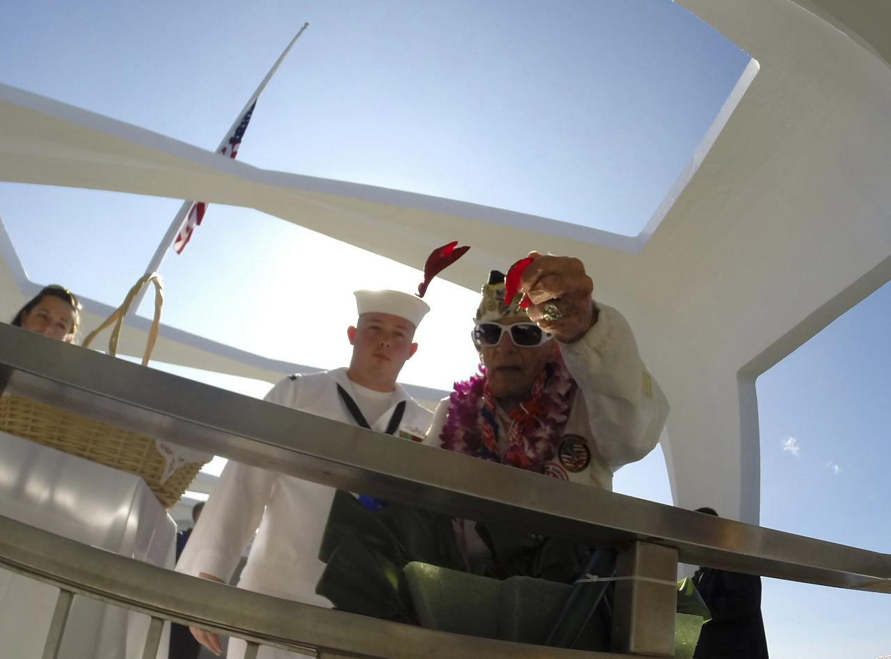 "Pearl Harbor survivor Allen Bodenlos drops rose pedals into the ""Rememberance Well"" as US Navy CTR1 Michael Temple watches while aboard the USS Arizona Memorial during the 72nd anniversary of the attack on Pearl Harbor at the WW II Valor in the Pacific National Monument in Honolulu, Hawaii on December 7, 2013. REUTERS/Hugh Gentry (UNITED STATES - Tags: ANNIVERSARY MILITARY SOCIETY TPX IMAGES OF THE DAY)"