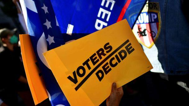 PHOTO: A 'Voters Decide' sign is pictured as people demonstrate outside of the Philadelphia Convention Center, where votes are still being counted two days after the 2020 U.S. presidential election, in Philadelphia, Pennsylvania. (Mark Makela/Reuters)