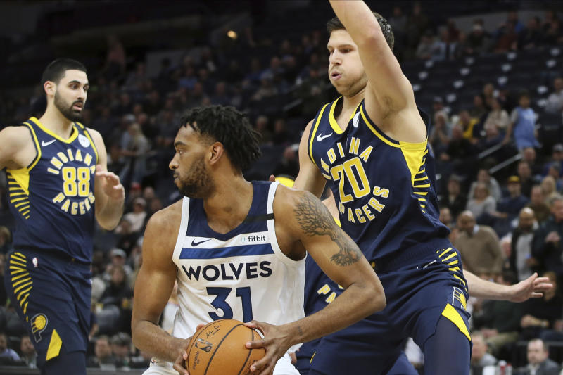 Minnesota Timberwolves' Keita Bates-Diop, center, looks for help as Indiana Pacers' Doug McDermott, right, looms over him in the first half of an NBA basketball game Wednesday, Jan. 15, 2020, in Minneapolis. (AP Photo/Jim Mone)