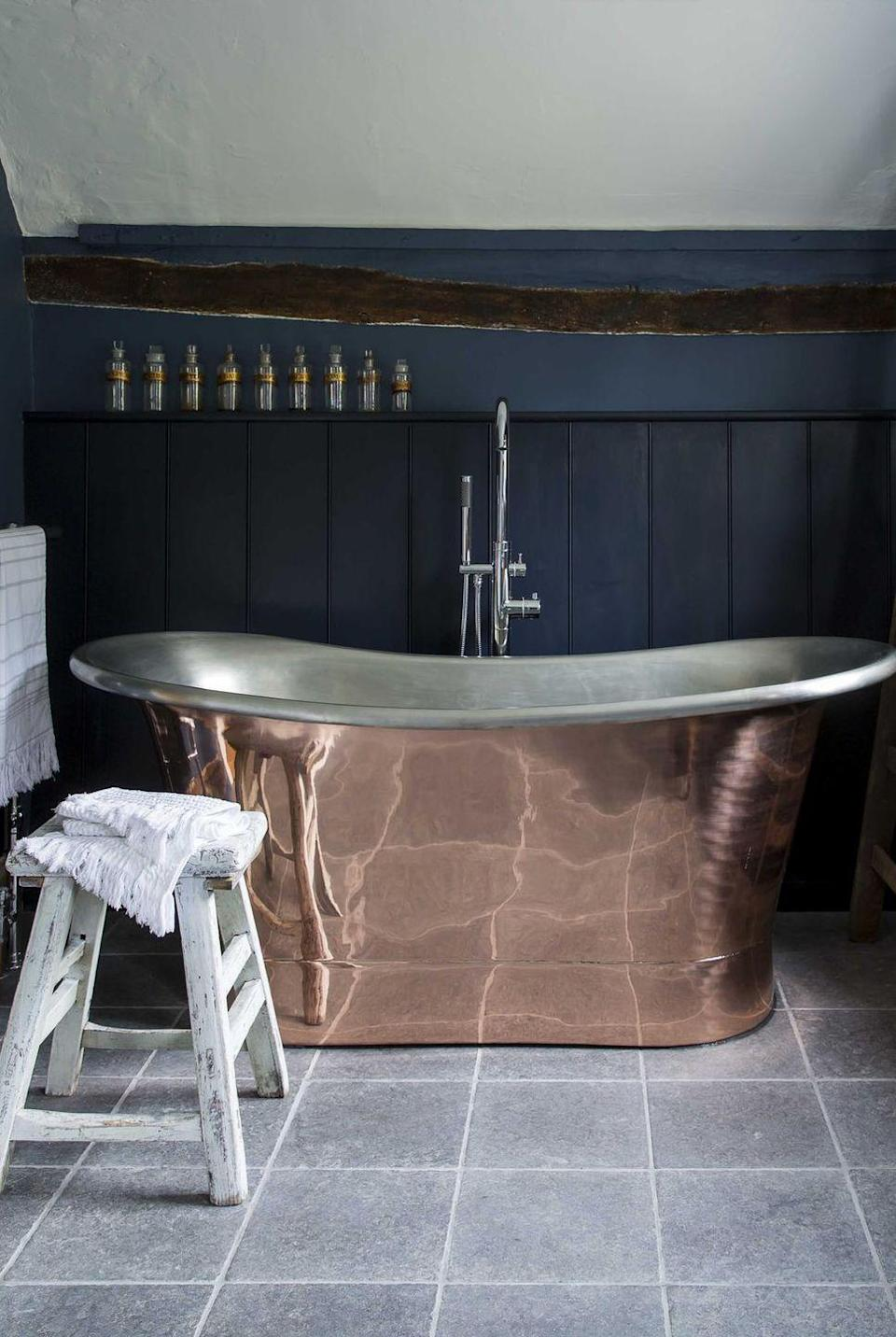 <p>Gray floor tiles contrast beautifully with the copper soaking tub and deep navy wall. </p>