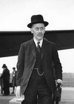Man in three-piece suit and hat carrying briefcase and umbrella with aircraft in the background.