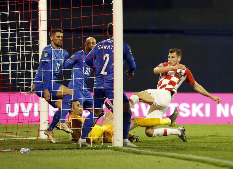 Croatia's Borna Barisic, right, scores his side's opening goal during the Euro 2020 group E qualifying soccer match between Croatia and Azerbaijan at the Maksimir stadium in Zagreb, Croatia, Thursday, March 21, 2019. (AP Photo/Darko Bandic)