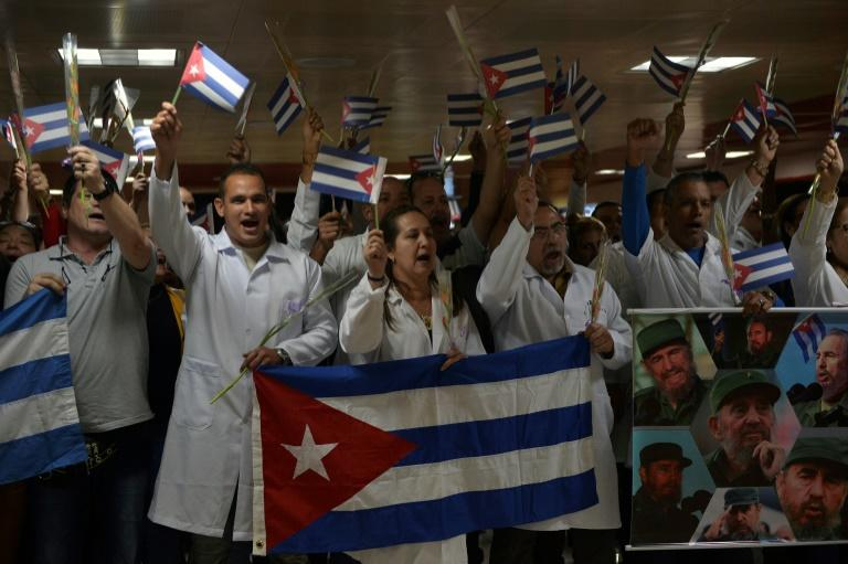 Doctors wait for fellow medical personnel returning from Bolivia at the Jose Marti International airport in Havana on November 16, 2019