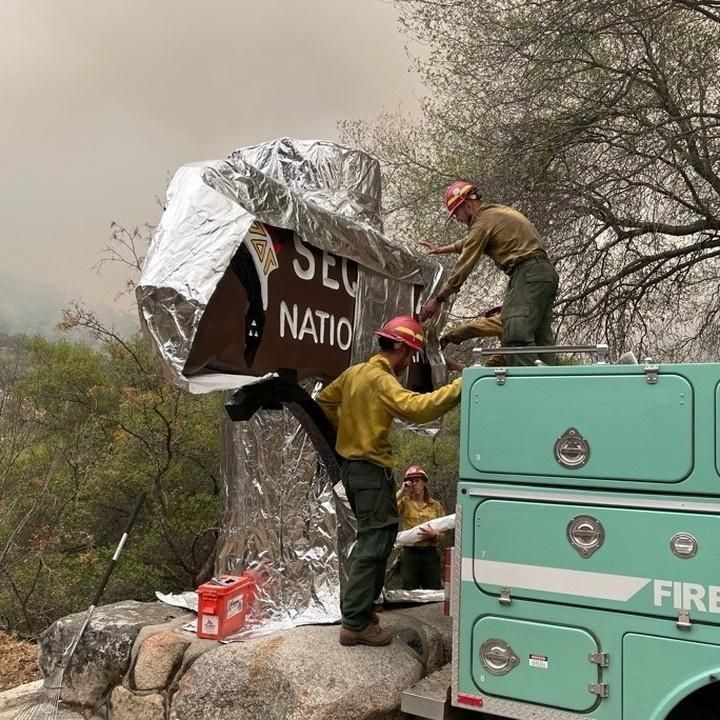 Firefighters cover a sign at Sequoia National Park