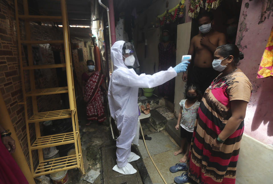 A health worker checks the temperature of a woman during a free medical checkup in a slum in Mumbai, India, Sunday, June 28, 2020. India is the fourth hardest-hit country by the COVID-19 pandemic in the world after the U.S., Russia and Brazil. (AP Photo/Rafiq Maqbool)
