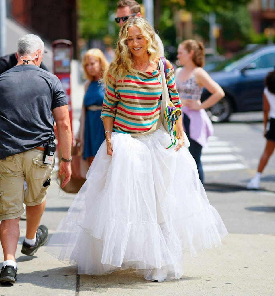 """<p>While on the set of And Just Like That in New York in August, the actor wore a floor length tutu which immediately took us back to the days of Carrie Bradshaw's ballerina-inspired look in the opening credits of Sex and The City.</p><p>For the appearance, the star styled the tutu with a colourful striped top, white Chanel ankle boots and a purple sequinned handbag.<br></p><p>She later shared a <a href=""""https://www.instagram.com/p/CSwcEEwLTJq/"""" rel=""""nofollow noopener"""" target=""""_blank"""" data-ylk=""""slk:video"""" class=""""link rapid-noclick-resp"""">video</a> of her skirt and boots on her Instagram, with the caption: 'Now and then. X, SJ.' Her followers soon took to the post's comments section, writing 'iconic' and 'Omg the chanel boots [sic].'</p>"""