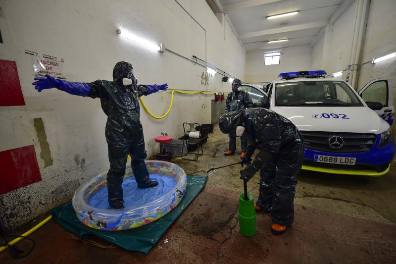 Volunteer workers of Search and Rescue (SAR) with special equipment, disinfect a volunteer after disinfecting a police car at Local Police station to prevent the spread of coronavirus COVID-19, in Pamplona, northern Spain, Sunday, March 22, 2020. For some people the COVID-19 coronavirus causes mild or moderate symptoms, but for some it causes severe illness. (AP Photo/Alvaro Barrientos)