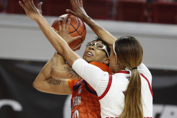 Clemson's Gabby Elliott (10) shoots as North Carolina State's Jakia Brown-Turner (11) defends during the first half of an NCAA college basketball game at Reynolds Coliseum in Raleigh, N.C., Thursday, Feb. 11, 2021. (Ethan Hyman/The News & Observer via AP)