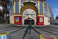 A man wearing a mask walks past Luna Park in the suburb of St Kilda during lockdown in Melbourne, Australia, Wednesday, Aug. 5, 2020. People are allowed to exercise for one hour a day within a 5-kilometer radius of their house. Victoria state, Australia's coronavirus hot spot, announced on Monday that businesses will be closed and scaled down in a bid to curb the spread of the virus. (AP Photo/Asanka Brendon Ratnayake)
