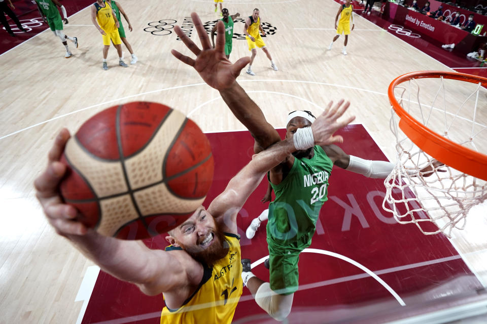Australia's Aron Baynes, left, drives to the basket against Nigeria's Josh Okogie (20) during a men's basketball preliminary round game at the 2020 Summer Olympics, Sunday, July 25, 2021, in Saitama, Japan. (AP Photo/Eric Gay)
