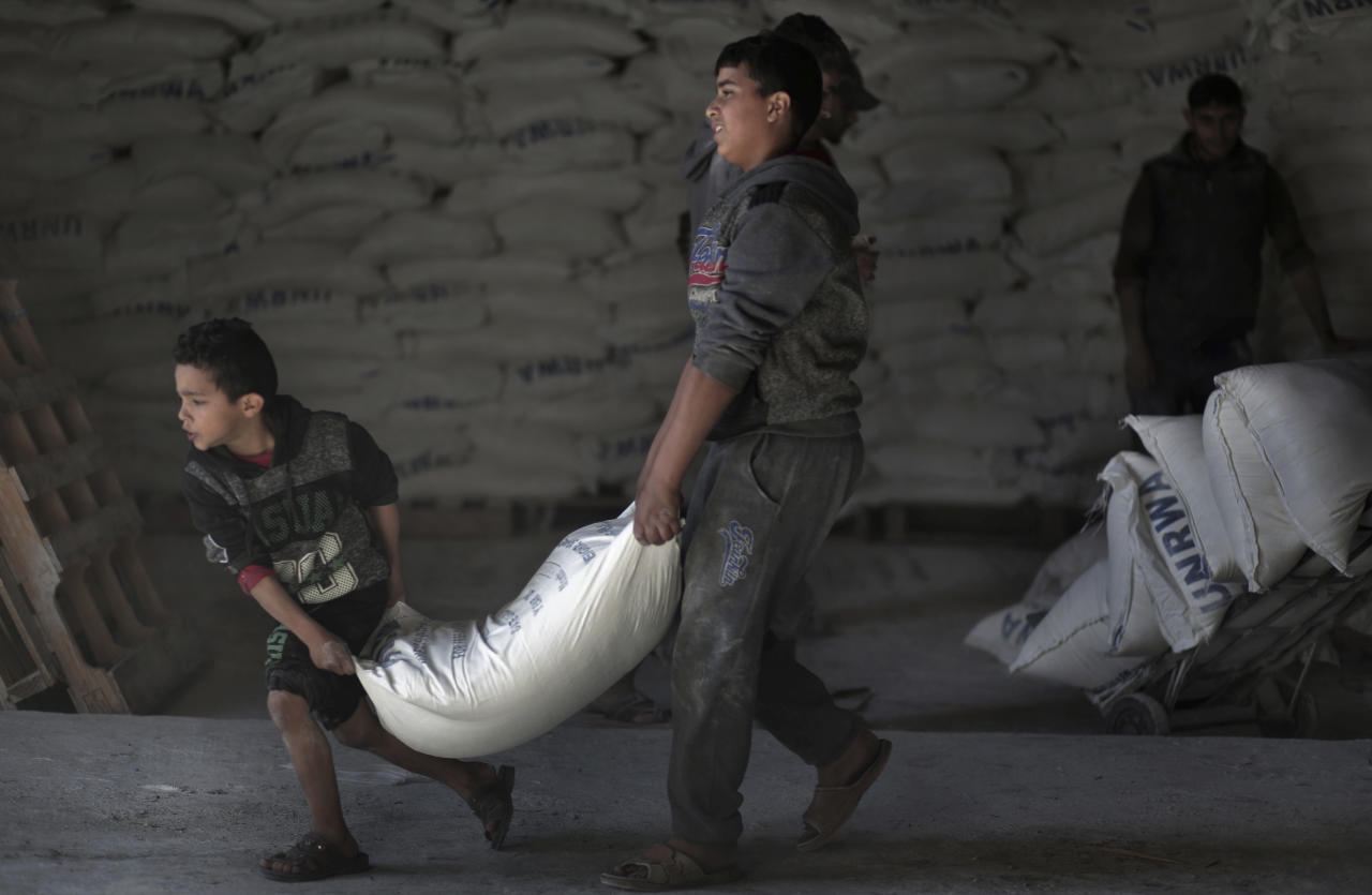 <p> In this Sunday Jan. 14, 2018 photo, Palestinians receive food aid at a U.N. warehouse in the Shati refugee camp, Gaza City. From the Gaza Strip to Jordan and Lebanon, millions of Palestinians are bracing for the worst as the Trump administration moves toward cutting funding to the U.N. agency that assists Palestinian refugees across the region. The expected cuts could deliver a painful blow to some of the weakest populations in the Middle East and risk destabilizing the already struggling countries that host displaced Palestinian refugees and their descendants. (AP Photo/ Khalil Hamra) </p>