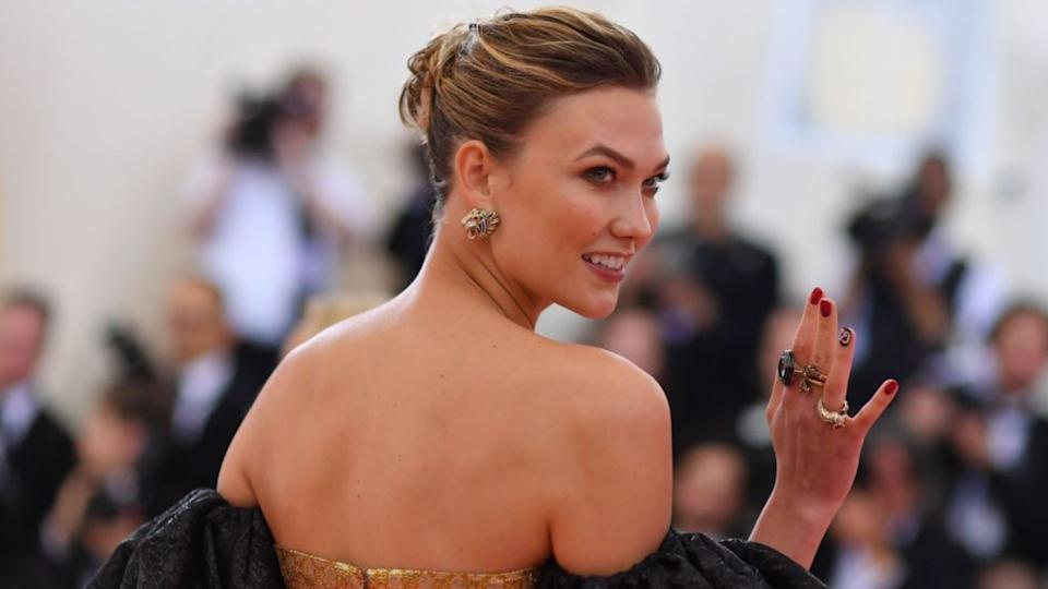 Karlie Kloss waves at cameras while attending the Met Gala.