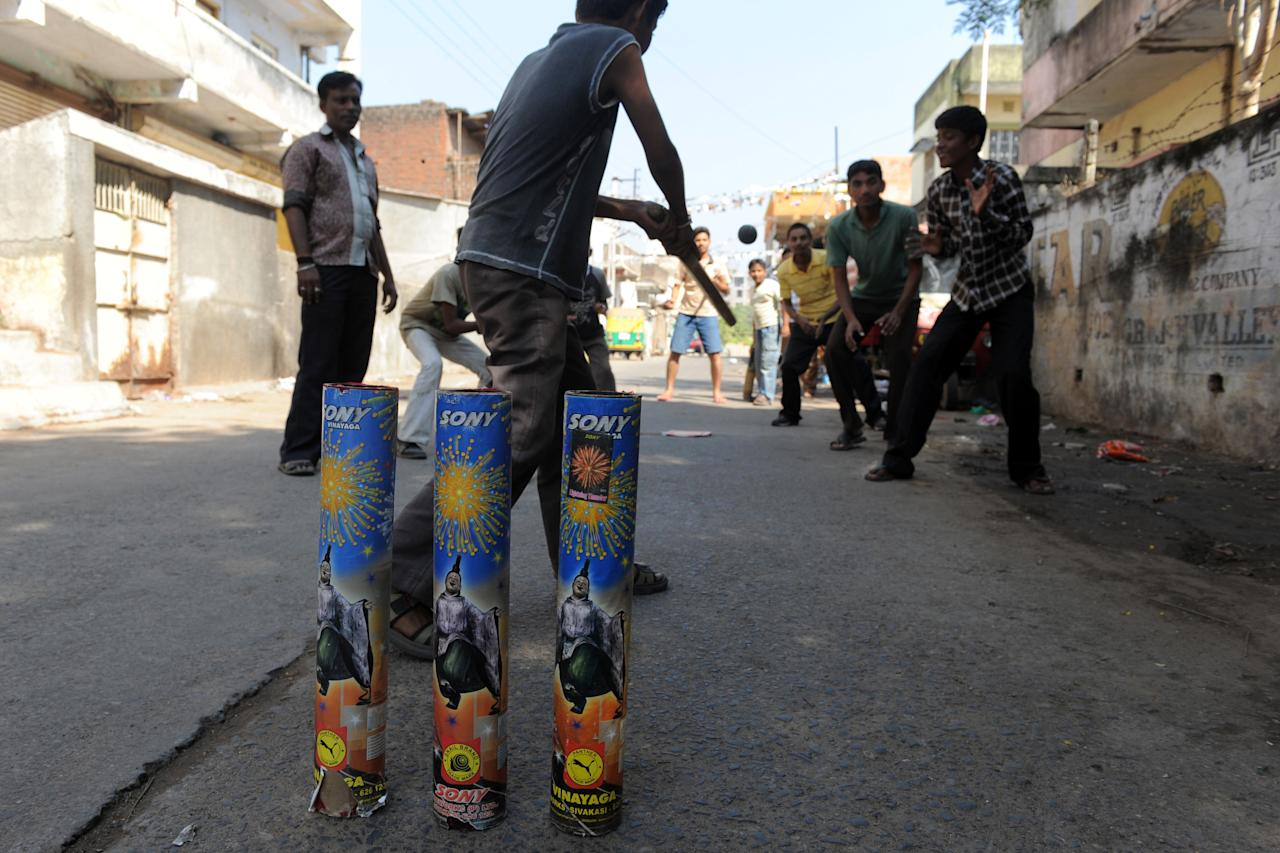Indian youths play street cricket using spent firecracker shells as improvised stumps in Nadiad town, some 60 kms from Ahmedabad, on October 29, 2011. Indian youths can often be seen playing the sport with parks and alleyways serving as makeshift grounds in the cricket-mad country. AFP PHOTO / Sam PANTHAKY (Photo credit should read SAM PANTHAKY/AFP/Getty Images)