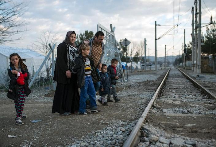 A migrant family crosses the Greek-Macedonian border near the town of Gevgelija on February 19, 2016 (AFP Photo/Robert Atanasovski)