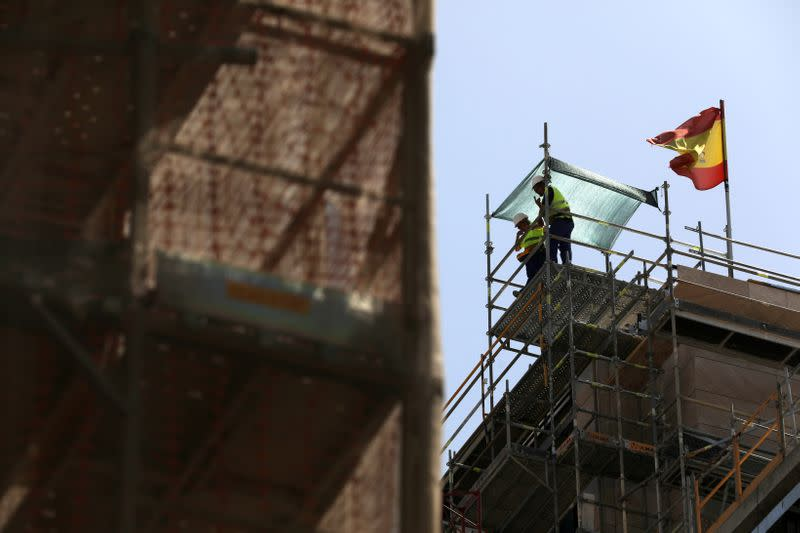 FILE PHOTO: Workers stand next to a Spanish flag at a construction site in Madrid