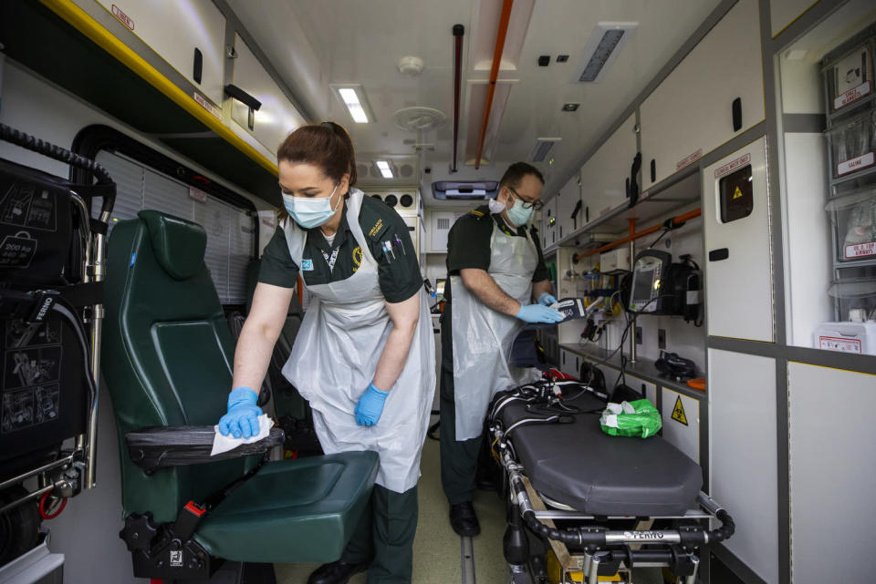 Ruth Corscadden and Daniel McCollam cleaning the ambulance after bringing a patient to the Causeway Hospital (Liam McBurney/PA)