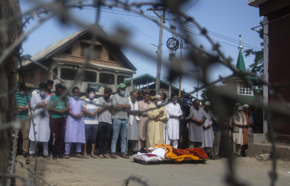 Relatives and neighbors offer funeral prayers near the body Bashir Ahmad, a civilian killed in a shootout, during his funeral at Sopore, 55 kilometers (34 miles) north of Srinagar, Indian controlled Kashmir, Saturday, June 12, 2021. Two civilians and two police officials were killed in an armed clash in Indian-controlled Kashmir on Saturday, police said, triggering anti-India protests who accused the police of targeting the civilians. (AP Photo/Mukhtar Khan)