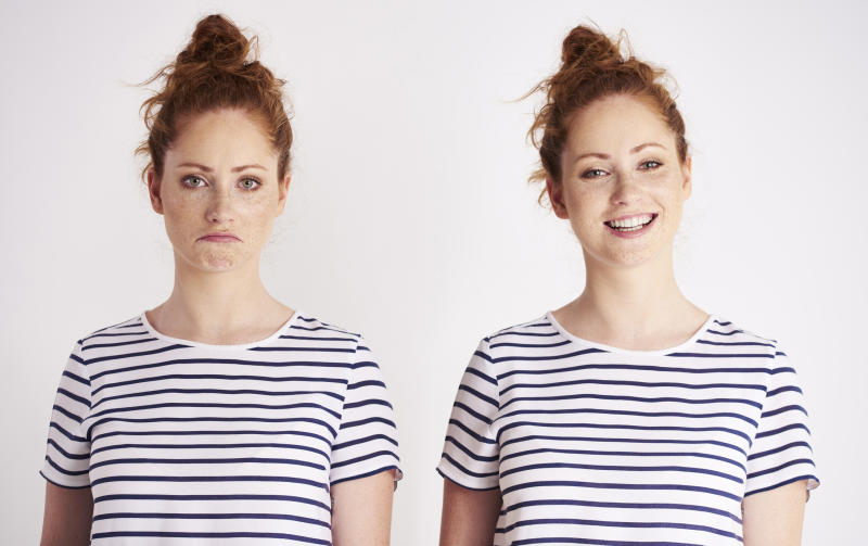 Two identical twin women next to each other, one of them sad and the other happy.