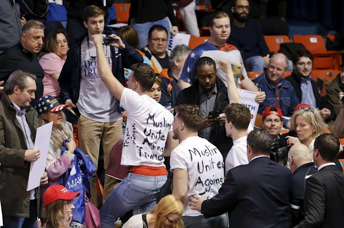 Protesters are escorted out of UIC Pavilion before Republican U.S. presidential candidate Donald Trump's rally at the University of Illinois at Chicago March 11, 2016. (REUTERS/Kamil Krzaczynski)