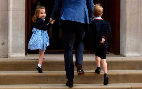 Princess Charlotte of Cambridge (left) turns to wave at the media as she is led in with her brother Prince George of Cambridge (right) - Credit: Ben Stansall/AFP