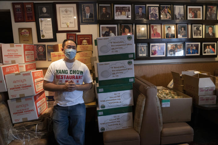Benny Yun, owner of Yang Chow stands inside his restaurant filled with supplies in Los Angeles, Thursday, Dec. 17, 2020. Bigotry toward Asian Americans and Asian food has spread steadily alongside the coronavirus in the United States. Yun said even though his businesses have survived the pandemic, they get prank calls almost daily asking if they have dog or cat on the menu or impersonating a thick Asian accent. (AP Photo/Damian Dovarganes)