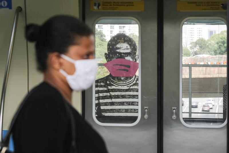 Artist Alex Flemming puts masks on portraits at the Sumare subway station, in the city of Sao Paulo, Brazil on May 6, 2020. The action is to warn about the importance of using face protection masks, preventing the spread and contagion of the new coronavirus that transmits Covid-19. (Photo by Fabio Vieira/FotoRua/NurPhoto via Getty Images)