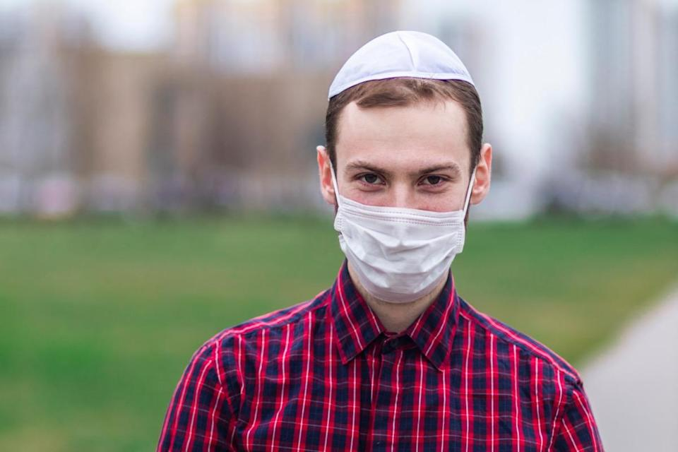 Young Jewish man in traditional jewish male headdress, wearing face mask outdoor.