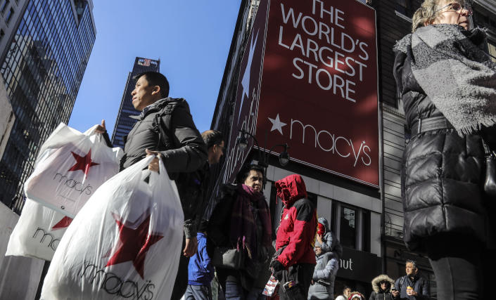 A shopper leaves Macy's department store with bags in both hands during Black Friday shopping, Friday, Nov. 29, 2019, in New York. (AP Photo/Bebeto Matthews)
