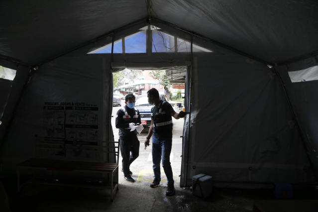 """Arun Saiju, right, of the RNA-16 volunteer group, coordinates with teammate Rajesh Gaiju at a hospital in Bhaktapur, Nepal, Tuesday, May 26, 2020. RNA-16 stands for """"Rescue and Awareness"""" and the 16 kinds of disasters they have prepared to deal with, from Nepal's devastating 2015 earthquake to road accidents. But the unique services of this group of three men and a woman in signature blue vests in the epidemic amount to a much greater sacrifice, said doctors, hospital officials and civic leaders. (AP Photo/Niranjan Shrestha)"""