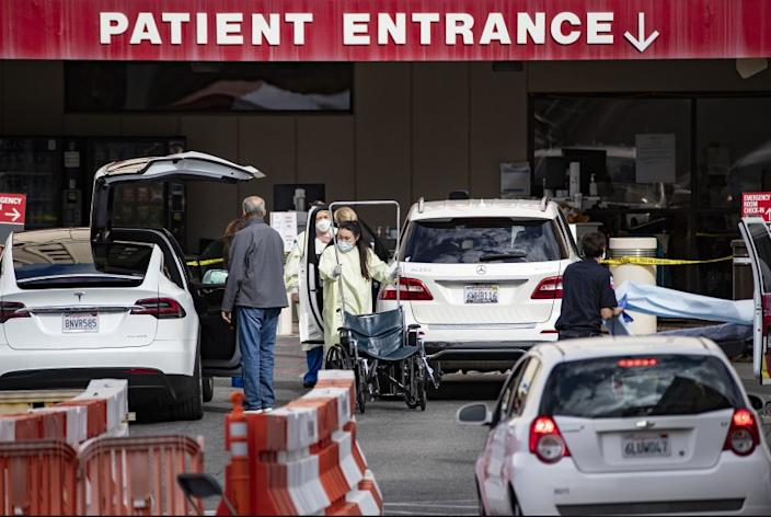 """Medical personnel tend to patients before screening them outside the Emergency Room at Loma Linda University Medical Center. <span class=""""copyright"""">(Gina Ferazzi/Los Angeles Times)</span>"""