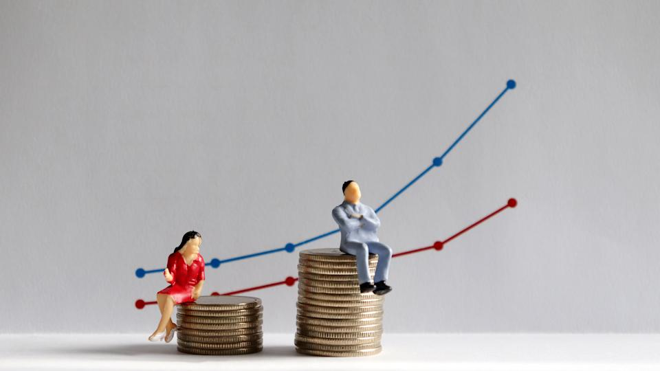 The concept of gender pay gap. A miniature man and a miniature woman sitting on top of a pile of coins at different heights in front of a bar graph. Photo: Getty