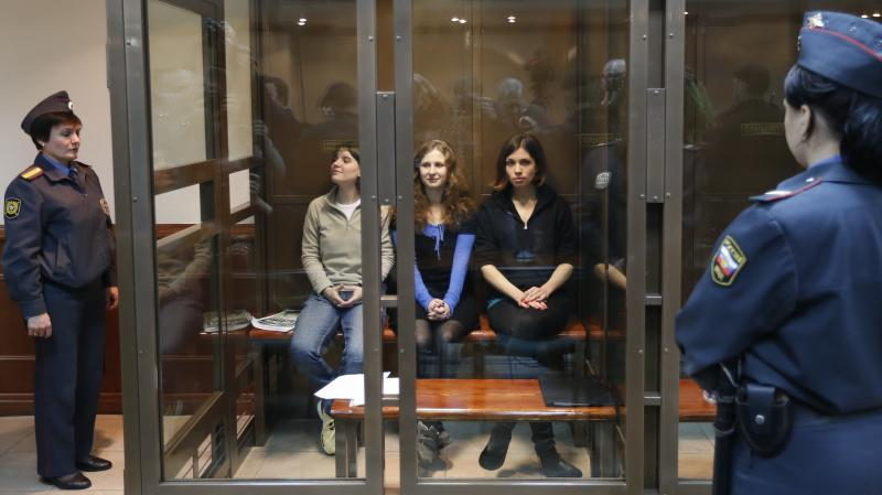 FILE - In this Wednesday, Oct. 10, 2012 file photo feminist punk group Pussy Riot members, center from left, Yekaterina Samutsevich, Maria Alekhina, and Nadezhda Tolokonnikova sit in a glass cage at a court room in Moscow. Russia's Prime Minister Dmitry Medvedev said Friday Nov. 2, 2012 that he detested the Pussy Riot act, but added the women have been in prison long enough and should be released. (AP Photo/Sergey Ponomarev, file)