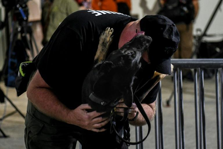 A K-9 handler greets a specially trained dog that detects coronavirus in people at the American Airlines Arena prior to the NBA basketball match between Miami Heat and the LA Clippers in Miami, on January 28, 2021