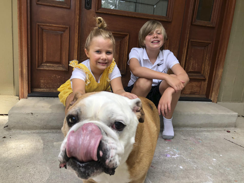 This image released by Jennifer Asbury shows her kids, Luca Asbury, 6, left, and her brother Will Asbury, 8, with their dog Drake in Littleton, Colo. Will Asbury is going into third grade. School starts Aug. 24 and he'll be there in person. There was a distance learning option but Will and his little sister, Luca, wanted to go. (Jennifer Asbury via AP)