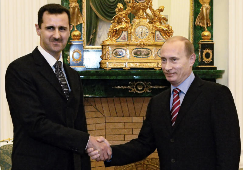 FILE - In this Tuesday, Dec. 19, 2006 file photo, Vladimir Putin, Russian President, right, and his Syrian counterpart Bashar Assad smile as they shake hands in Moscow's Kremlin. In a few days' worth of opportunistic diplomacy, Vladimir Putin has revived memories of an era many thought long gone, where the United States and Soviet Union jostled for influence in a Middle East torn between two powers. Whatever happens with its proposal to relieve Syria of chemical weapons, Russia reemerges as a player in the region _ and one who does not easily abandon allies. That's meaningful in a region where America's dumping of Hosni Mubarak has emerged as a seminal moment _ and it may resonate with Iran, whose leaders are carefully watching the global chessboard as the clock ticks toward another showdown, over their nuclear program.(AP photo/RIA Novosti, Mikhail Klimentyev, Presidential Press service, File)