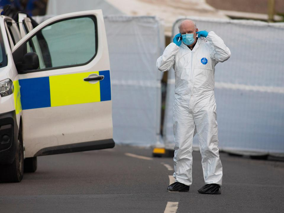 <p>A forensic officer is seen on Baglan Street, Treorchy, after Friday's incident </p> (EPA)