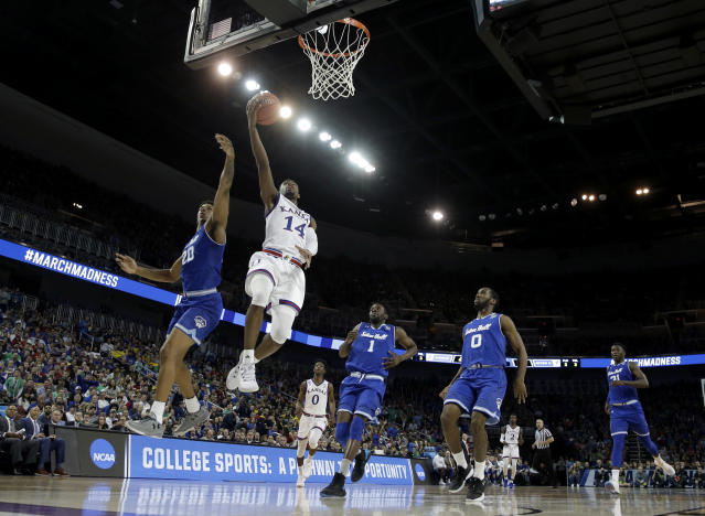 Kansas guard Malik Newman (14) gets pst Seton Hall forward Desi Rodriguez (20) to put up a shot during the second half of an NCAA men's college basketball tournament second-round game Saturday, March 17, 2018, in Wichita, Kan. Kansas won 83-79. (AP Photo/Charlie Riedel)
