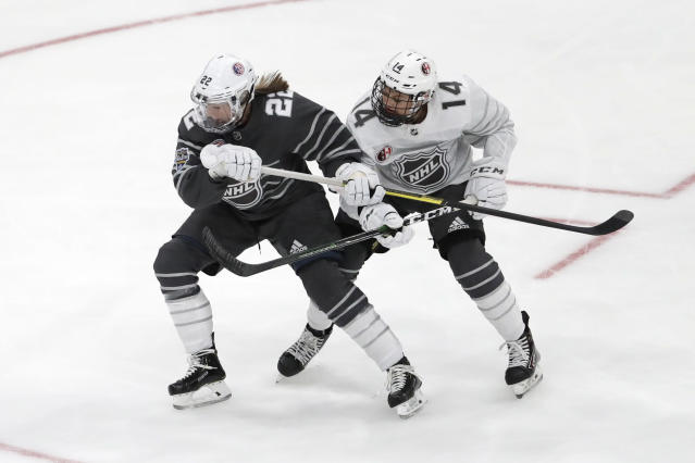 United States' Kacey Bellamy (22) and Canada's Renata Fast (14) battle for the puck during the first period in the women's 3-on-3 game, part of the NHL hockey All-Star weekend, Friday, Jan. 24, 2020, in St. Louis. (AP Photo/Jeff Roberson)