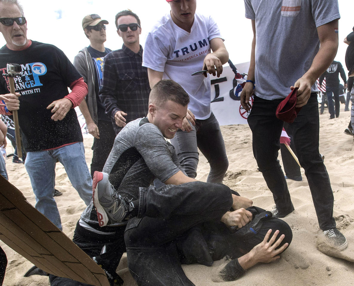 <p>A supporter of President Donald Trump, center, clashes with an anti-Trump protester, bottom center, in Huntington Beach, Calif., on Saturday, March 25, 2017. Violence erupted when a march of about 2,000 Trump supporters at Bolsa Chica State Beach reached a group of about 30 counter-protesters, some of whom began spraying pepper spray, said Capt. Kevin Pearsall of the California State Parks Police. (Mindy Schauer/The Orange County Register via AP) </p>
