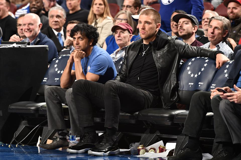 M. Night Shyamalan and NFL player Zach Ertz attend Game Two of Round One between the Brooklyn Nets and the Philadelphia 76ers during the 2019 NBA Playoffs on April 15, 2019 at the Wells Fargo Center in Philadelphia, Pennsylvania. (Photo by David Dow/NBAE via Getty Images)