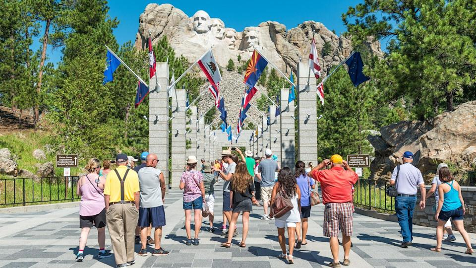 The Entrance of the Mount Rushmore National Monument on a sunny summer day with tourists and taking photographs of the view, Black Hills National Forest, South Dakota, USA.