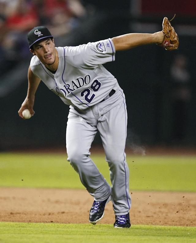 In this July 5, 2013, photo, Colorado Rockies third baseman Nolan Arenado looks to first after fielding a grounder by the Arizona Diamondbacks during a baseball game in Phoenix. Arenado became the 10th rookie to win a Gold Glove and first since Seattle outfielder Ichiro Suzuki in 2001. (AP Photo/Rick Scuteri)