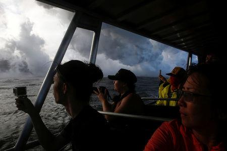 People watch as lava flows into the Pacific Ocean southeast of Pahoa during ongoing eruptions of the Kilauea Volcano in Hawaii, U.S., May 20, 2018.   REUTERS/Terray Sylvester