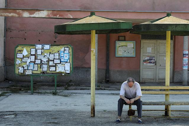 <p>Death notices are seen on a notice board as a man sits at a bus station in the village of Kalna, near the southeastern town of Knjazevac, Serbia, Aug. 15, 2017. (Photo: Marko Djurica/Reuters) </p>