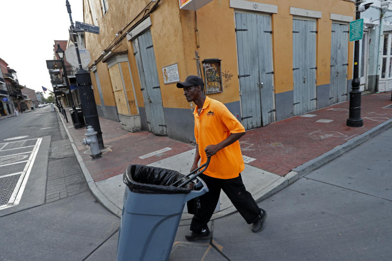 A worker pushed s trash can on a largely empty Bourbon Street, due to the coronavirus pandemic, in the French Quarter of New Orleans, Tuesday, May 12, 2020. Attempts to curb the spread of COVID-19 have visited a kind of triple economic whammy on the state.   (AP Photo/Gerald Herbert)