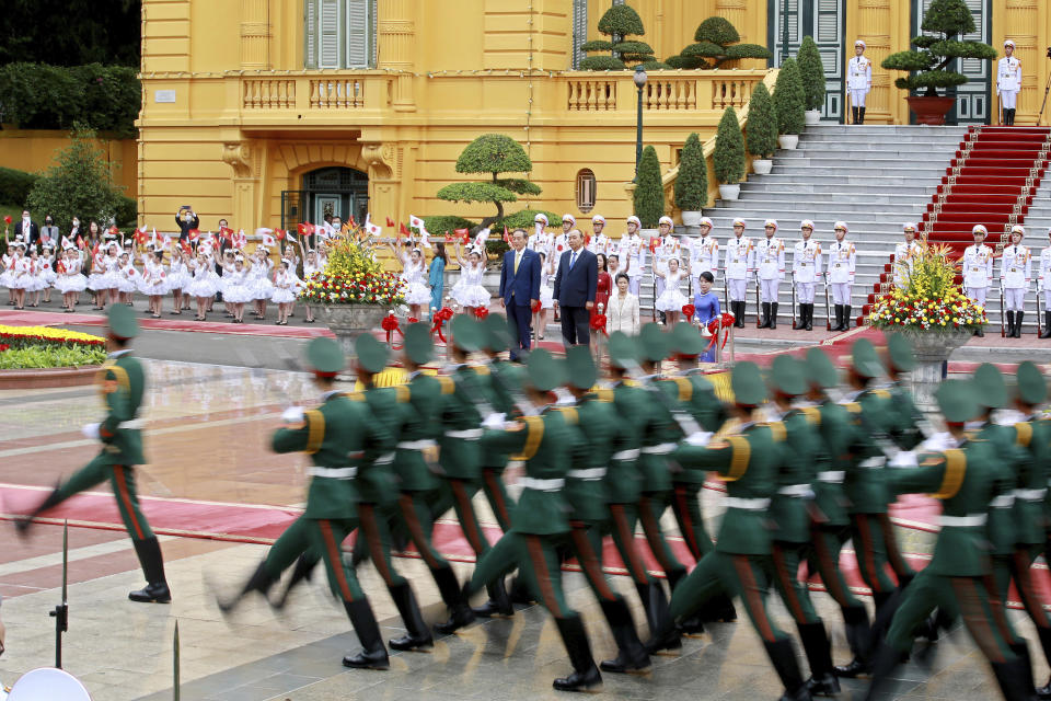 Japanese Prime Minister Yoshihide Suga, center left, and his Vietnamese counterpart Nguyen Xuan Phuc, center right, review an honor guard at the Presidential Palace in Hanoi, Vietnam Monday, Oct. 19, 2020. Suga is on an official visit to Vietnam. (AP Photo/Minh Hoang, Pool)