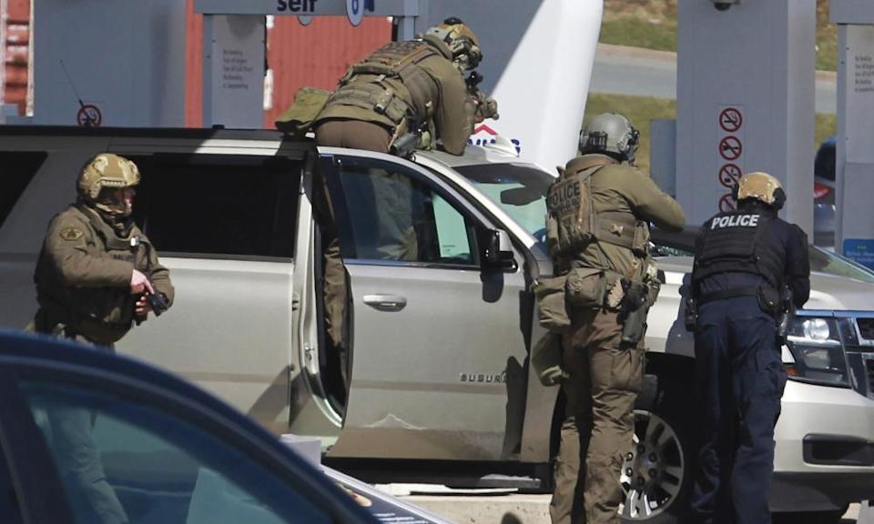 Royal Canadian Mounted Police officers surround a suspect at a gas station in Enfield, Nova Scotia.